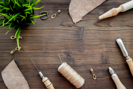 Leather craft. Tanners tools on dark wooden table