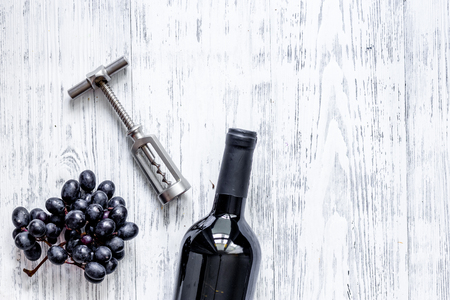 Open wine. Bottle and corkscrew on light wooden table background top view.
