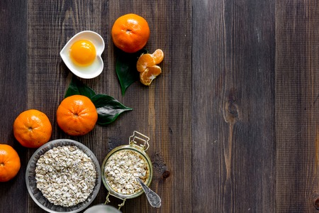 Sweet summer breakfast. Oatmeal, oranges, sugar on wooden table background top view. Banco de Imagens