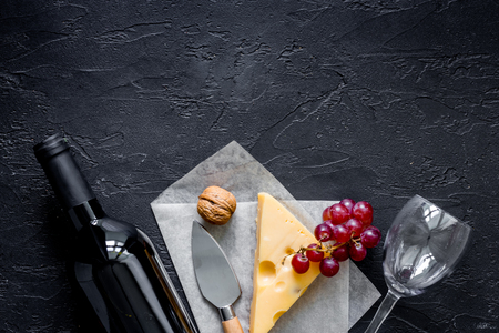 Wine snack. Cheese, nuts, grape on black stone table background top view
