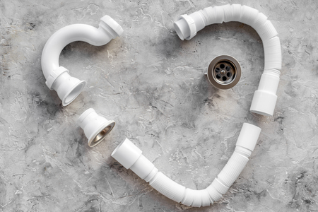 Disassembled sink drain pipe heart shaped on grey stone background top view copyspace