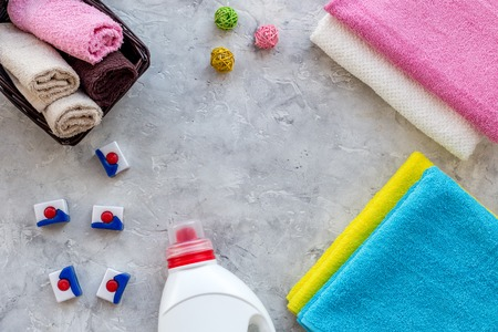 Housework. Wash clothes. Dry and liquid detergents near clean towel on grey stone background top view copyspace