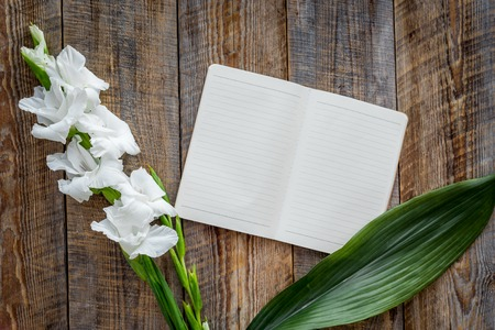 Feminine desk workspace. Notebook and gladiolus on wooden background top view.