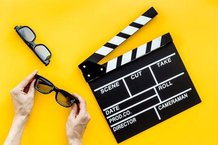 Filmmaker accessoires. Klapbord en glazen op geel achtergrond bovenaanzicht.