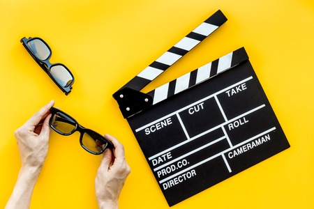 filmmaker: Filmmaker accessories. Clapperboard and glasses on yellow background top view.