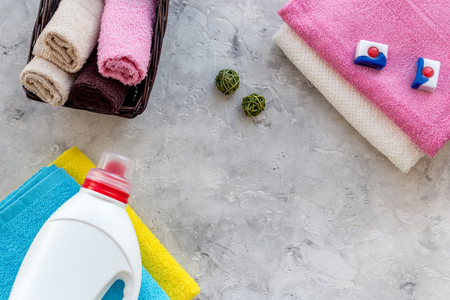 Liquid detergent near clean towel on grey stone background top view. Stock Photo - 83591823