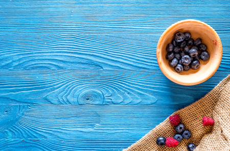 Paspberry and blueberry for preparing jam on blue wooden background top view. Stock Photo