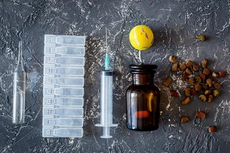Diergeneeskunde concept. Pillen en diervoeder op grijze steen achtergrond bovenaanzicht.
