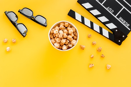 filmmaker: Ready to watch film. Clapperboard, glasses and popcorn on yellow background top view. Stock Photo