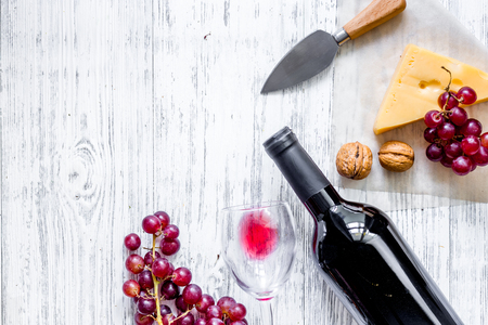 Wine snack. Cheese, nuts, grape on light wooden table background top view