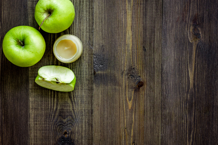 Apple puree for baby on dark wooden background top view. Stock Photo