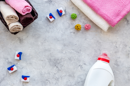 Dry and liquid detergents near clean towel on grey stone background top view. Stock Photo - 83656862