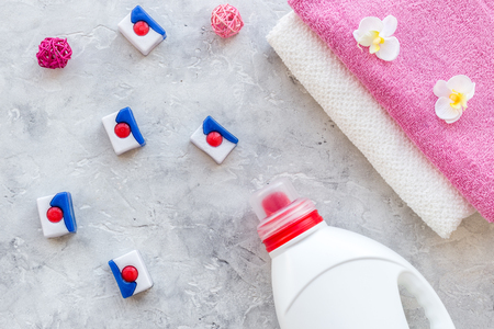 Dry and liquid detergents near clean towel on grey stone background top view. Stock Photo