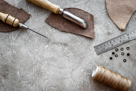 Leather craft. Tanners tools on grey stone background top view.