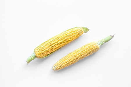 Organic corn on cobs on white background top view.