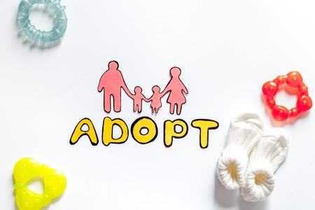 Adopt word, paper silhouette of family and toys on white background top view. 版權商用圖片 - 83719540