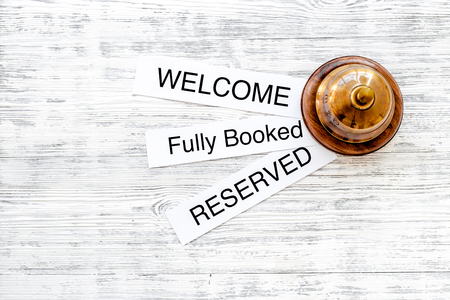 booked: At the hotel. Words welcome, fully booked, reserved on light wooden table top view.