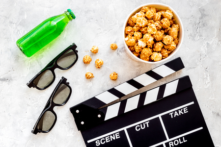 Nourriture pour regarder un film. Pop-corn et soda près de Clap, lunettes sur la vue de dessus de fond gris. Banque d'images - 83720350