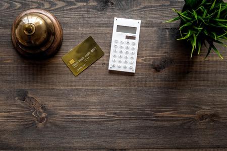 호텔 서비스 벨 어두운 나무 테이블 상위 뷰 은행 카드 근처.