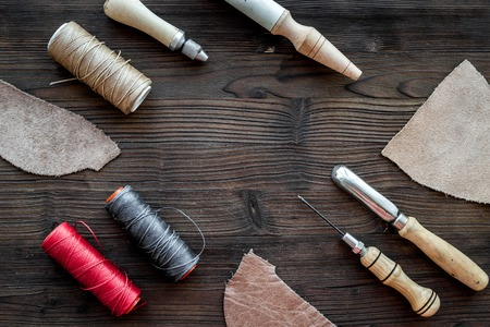 Leather craft. Knife, awl and other tools on dark wooden background top view. Zdjęcie Seryjne