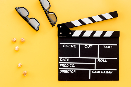Ready to watch film. Clapperboard, glasses and popcorn on yellow background top view. Stock Photo