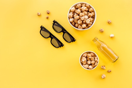 Snacks for film watching. Popcorn and soda near glasses on yellow background top view.