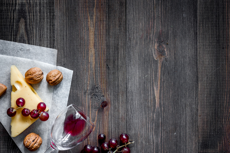 Wine snack. Cheese, nuts, grape on dark wooden table background top view Zdjęcie Seryjne