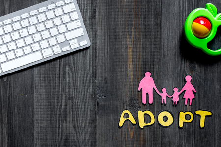 Adopt word, paper silhouette of family and toys near keyboard on dark wooden table background top view copyspace