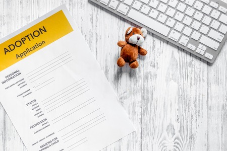 Adoption application near keyboard and toy on light wooden table background top view copyspace