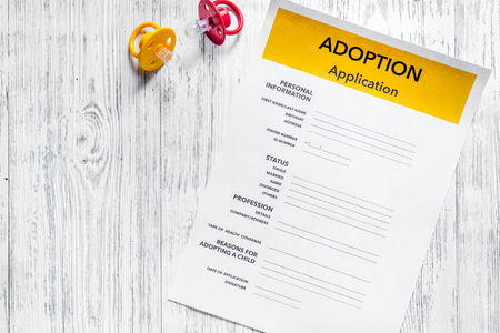 Adoption application near baby pacifier on light wooden table background top view copyspace