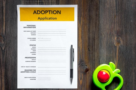 Adoption application near toy on dark wooden table background top view copyspace Stock Photo