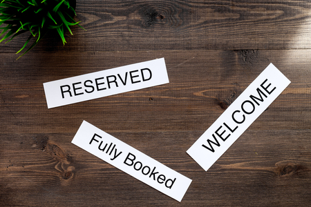booked: At the hotel. Words welcome, fully booked, reserved on dark wooden table top view copyspace Stock Photo
