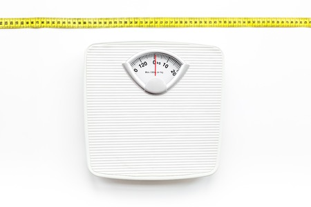Bathroom scale and measuring tape on white background top view