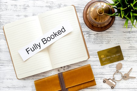 booked: Book hotel. Service bell and notebook with word fully booked at the reception on light wooden table top view