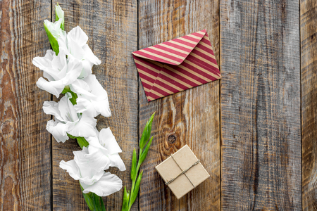 Congratulation. Envelope and box in kraft paper near flower gladiolus on wooden table top view copyspace Stock Photo