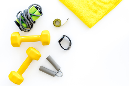 Fitness for loosing weight. Dumbbells, jump rope and measure tape on white background top view copyspace