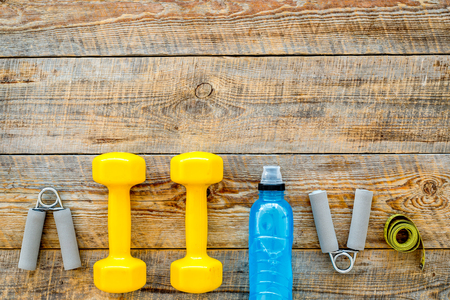 Fitness for losing weight. Dumbbells, expander, measure tape and water on wooden background top view copyspace