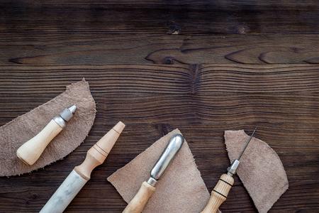 가죽 공예. 나이프, 송곳 및 어두운 나무 배경 상위 뷰에 다른 도구.