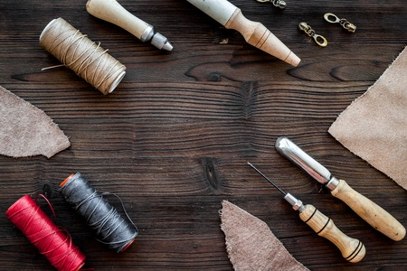 Leather craft. Knife, awl and other tools on dark wooden background top view copyspace