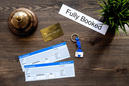 Preparing to trip. Book hotel and tickets. Tickets near service bell, bank card on dark wooden table top view copyspace Stok Fotoğraf