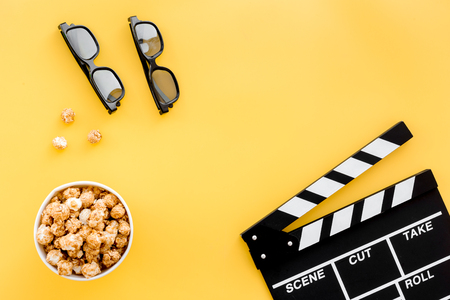 filmmaker: Ready to watch film. Clapperboard, glasses and popcorn on yellow background top view copyspace Stock Photo