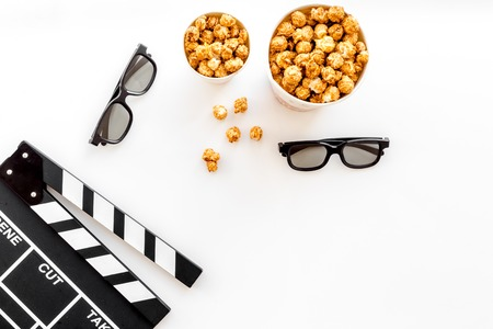 To go to the cinema. Clapperboard, glasses and popcorn on white background top view copyspace