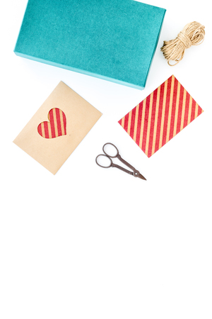 To wrap gift. Box, paper, envelope, thin cord, greeting card, ribbon, sciccors on white background top view Stock Photo