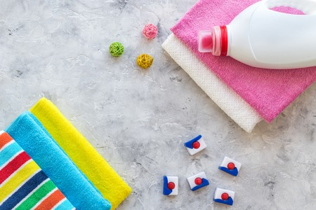 Dry and liquid detergents near clean towel on grey stone background top view. Stok Fotoğraf