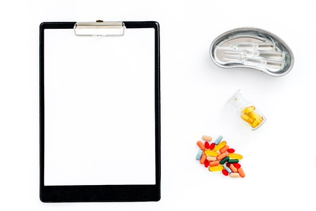 Doctors workplace in clinic. Clip pad, colored pills and cuvette with ampoulie on white background top view mockup
