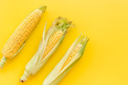 Corn on cobs on yellow background top view.