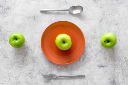 Slimming diet. Apple at plate on grey stone background top view Stock Photo