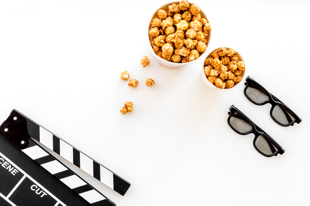 filmmaker: To go to the cinema. Clapperboard, glasses and popcorn on white background top view copyspace