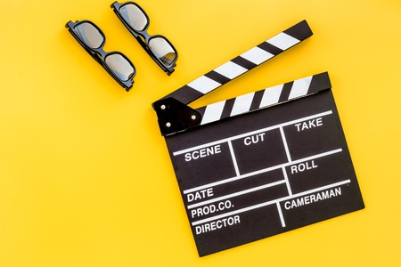 filmmaker: Filmmaker accessories. Clapperboard and glasses on yellow background top view copyspace Stock Photo