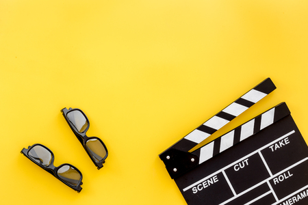 Filmmaker accessories. Clapperboard and glasses on yellow background top view copyspace Stock Photo